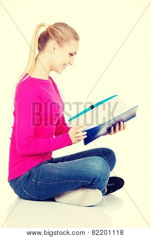 Young student woman sitting cross legged with workbook.