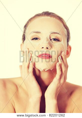 Beautiful spa woman with collagen mask on face.