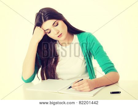 Young casual student woman writing in workbook.