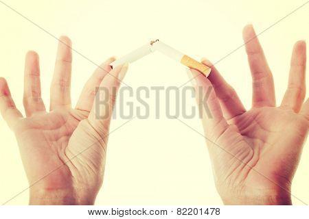 Broken cigarette in woman's hands. Smoking concept.