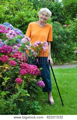 Smiling Senior Woman Standing At The Flower Garden