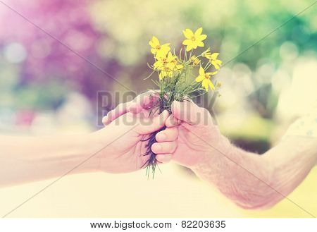 Elderly And Young Woman Holding Flowers Outside