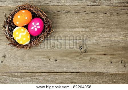 Easter eggs in nest on wood