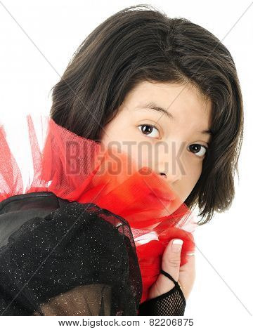 A shy young teen looking out at the viewer from being sheer red frills.  On a white background.