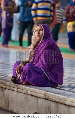 Indian Women In Purple Sari Sitting Near The Lake At Golden Temple. Amritsar. India