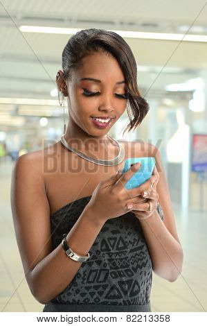 Portrait of African American woman using cellphone indoors