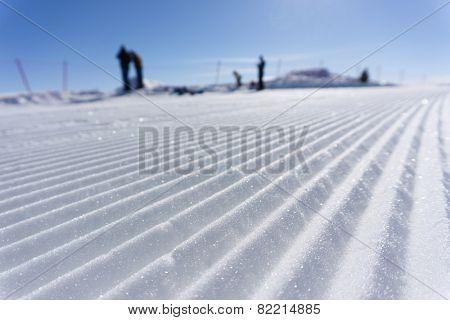 Fresh snow groomer tracks on a mountain ski piste