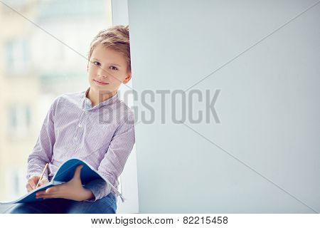Handsome schoolboy with exercise-book looking at camera