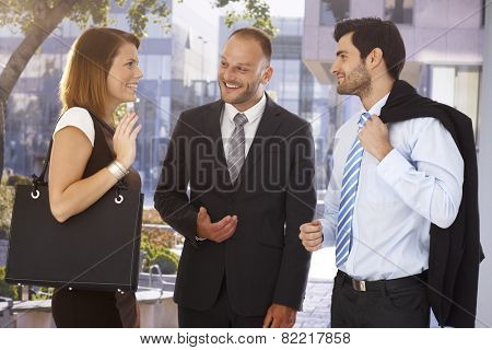 Happy businessman introducing new partner to attractive female colleague, outdoors. Suit and tie.
