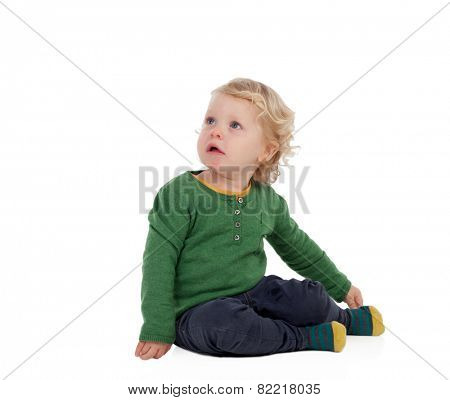 Adorable blond baby sitting on the floor isolated on a white background