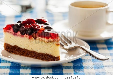 Dessert background - fruit cheese cake on plate with fork and coffee cup on blue checkered tablecloth