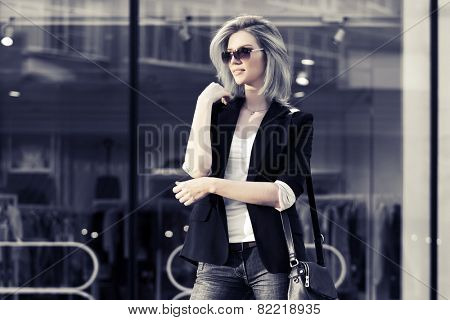 Young fashion blond business woman against a mall window