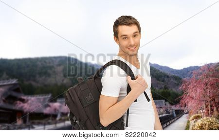 people, travel, tourism and education concept - happy young man with backpack and book travelling over asian landscape background