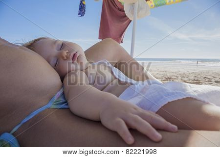 Baby Sleeping Above Mom At Beach