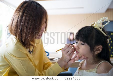 Professional Makeup Artist Working With Cute Asian Child