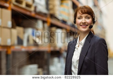 Smiling manager wearing a headset in a large warehouse