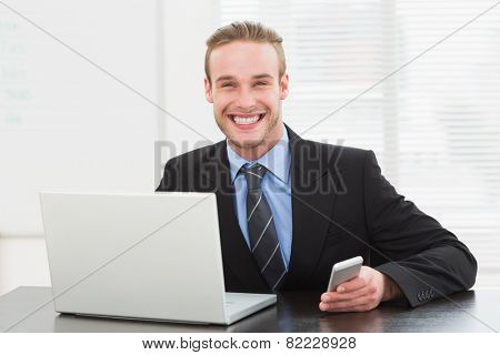 Classy businessman using laptop and mobile phone in his office