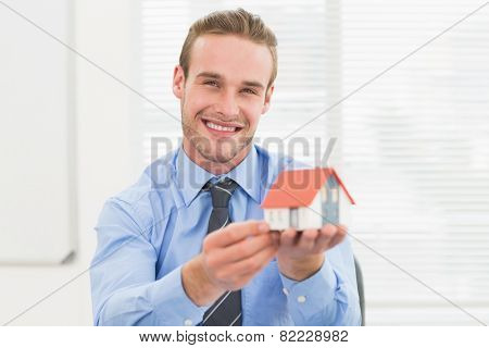 Happy businessman showing miniature house in his office