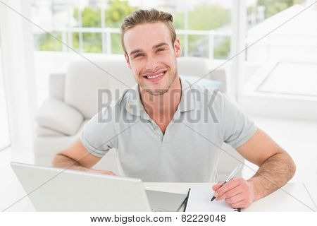 Smiling businessman using laptop and taking notes in his office