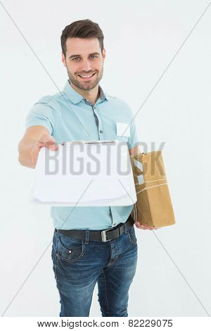 Portrait of happy delivery man with package giving clipboard for signature on white background
