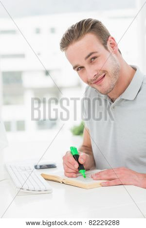 Cheerful casual businessman highlighting a book in his office