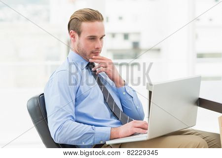 concentrated businessman using laptop in his office