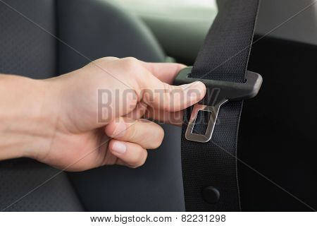 Man putting on his seat belt in his car