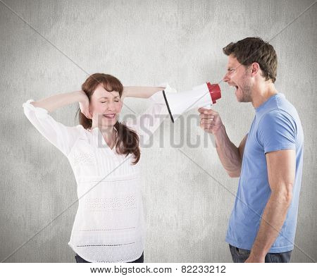Man shouting through a megaphone against weathered surface