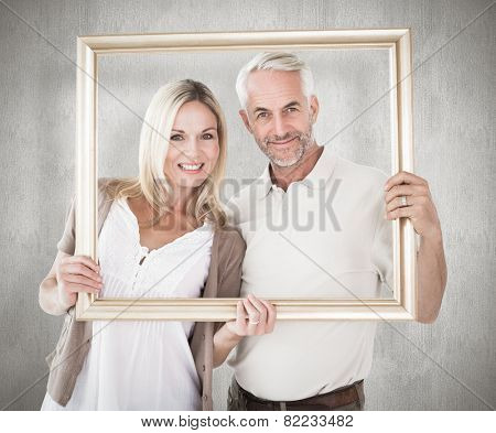 Happy couple holding a picture frame against weathered surface