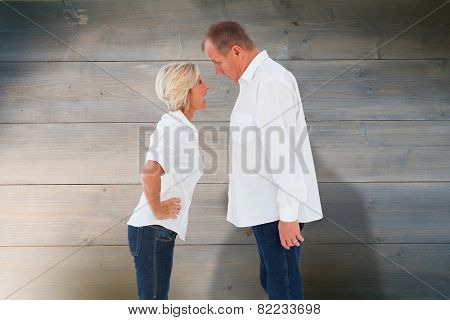 Angry older couple arguing with each other against bleached wooden planks background