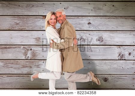 Happy couple posing in trench coats against digitally generated grey wooden planks