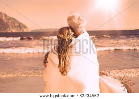 Couple wrapped up in blanket on the beach looking out to sea on a sunny day