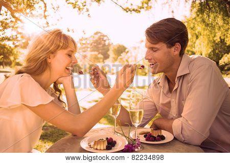Cute couple feeding each other dessert on a sunny day