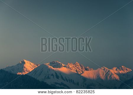 lighted mountain peaks with snow at winter in tirol