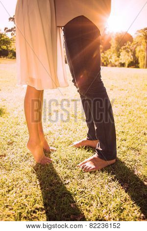 Couples bare feet standing on grass on a sunny day