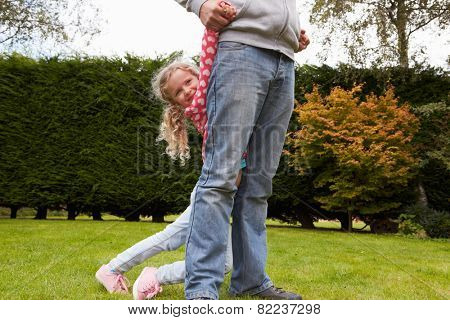 Father And Daughter Playing Game In Garden Together