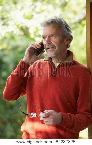 Mature Man Using Cordless Phone At Home