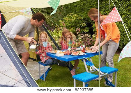 Family Enjoying Meal Outside Tent On Camping Holiday