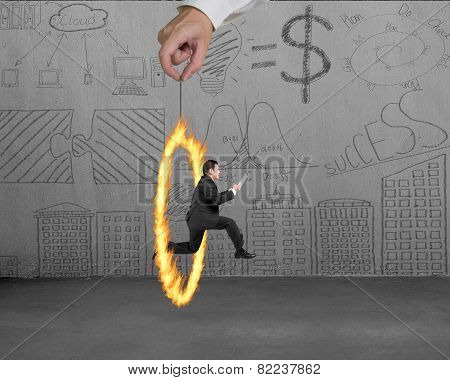 Businessman Jumping Through Fire Circle Hand Holding With Doodles Wall