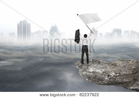 Businessman Cheering On Cliff Waving Flag With Cloudy Cityscape