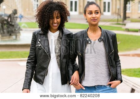 Two north African teen friends take a walk in the park talking