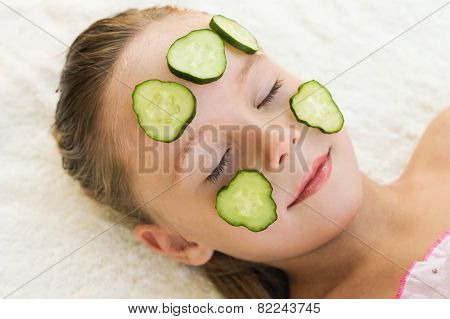 Close up of beautiful girl with facial mask of cucumber