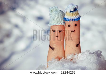 Finger art of a Happy couple on the background of snow. A man and a woman hug. Toned image.
