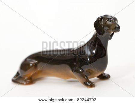Black smooth haired dachshund. Ceramic figurine, dog breed isolated on white