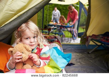 Girl With Teddy Bear Enjoying Camping Holiday On Campsite