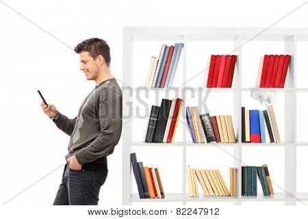 Man leaning on a bookshelf and typing on his phone isolated on white background