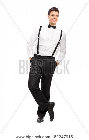 Full length portrait of a handsome guy with suspenders and bow-tie leaning against a wall isolated on white background