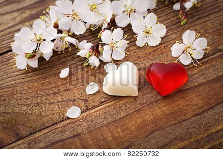 Wedding hearts. Spring. Flowering branch with white delicate flowers on  wooden surface.