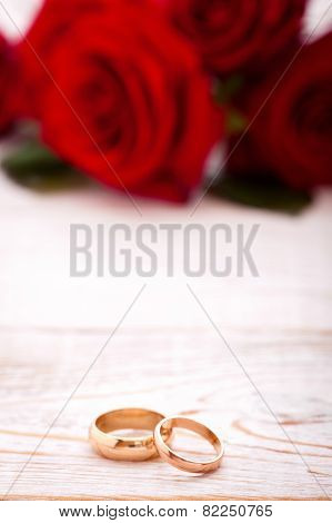 Wedding Rings And Wedding Bouquet Of Red Roses.