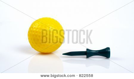 Yellow golfball and green tee with reflecting